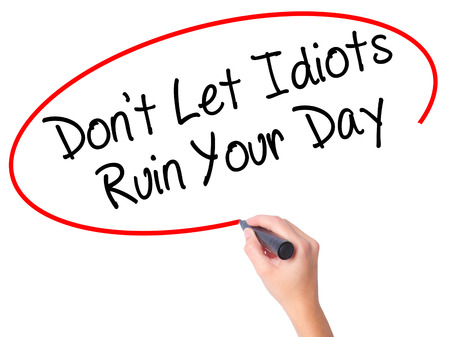 stupidity: Women Hand writing Dont Let Idiots Ruin Your Day with black marker on visual screen. Isolated on white. Business, technology, internet concept. Stock Photo