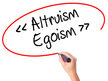 Women Hand writing Altruism - Egoism with black marker on visual screen. Isolated on white. Business, technology, internet concept. Stock Photo