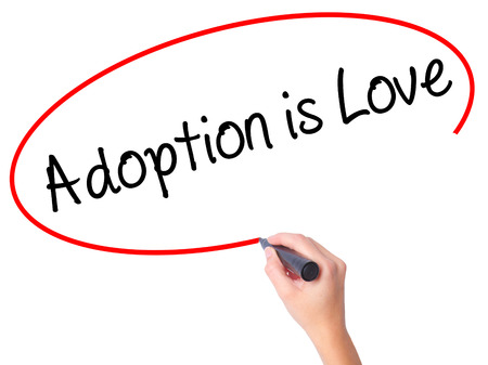 Women Hand writing Adoption is Love with black marker on visual screen. Isolated on white. Adoption, technology, internet concept. Stock Photo