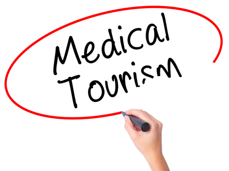 health care fees: Women Hand writing Medical Tourism with black marker on visual screen. Isolated on white. Business, technology, internet concept. Stock Photo Stock Photo