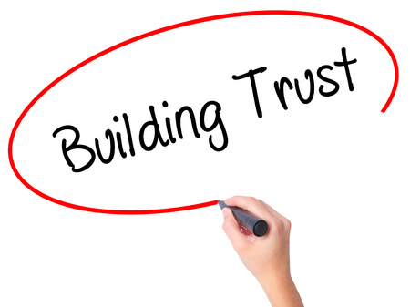 building trust: Women Hand writing Building Trust with black marker on visual screen. Isolated on white. Business, technology, internet concept. Stock Photo
