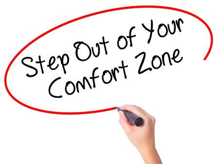 Women Hand writing Step Out of Your Comfort Zone with black marker on visual screen. Isolated on white. Business, technology, internet concept. Stock Photo