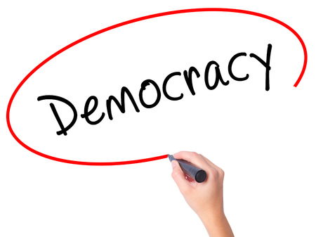 Women Hand writing Democracy with black marker on visual screen. Isolated on white. Business, technology, internet concept. Stock Image Stock Photo