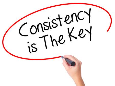 Vrouwen Hand schrijven Consistentie is de sleutel met zwarte stift op visuele scherm. Geïsoleerd op wit. Business, technologie, internet concept. Stock foto
