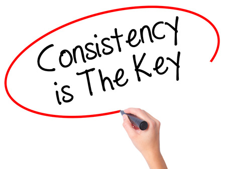 consistency: Women Hand writing Consistency is The Key with black marker on visual screen. Isolated on white. Business, technology, internet concept. Stock Photo Stock Photo