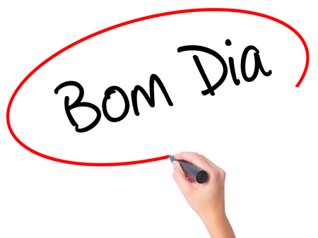 """Women Hand writing """"Bom Dia"""" (In portuguese - Good Morning)  with black marker on visual screen. Isolated on white. Business, technology, internet concept. Stock Photo"""