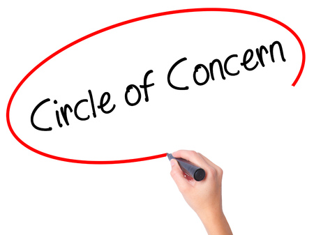 Women Hand writing Circle of Concern with black marker on visual screen. Isolated on white. Business, technology, internet concept. Stock Photo