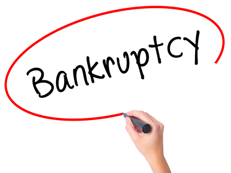 Women Hand writing Bankruptcy with black marker on visual screen. Isolated on white. Business, technology, internet concept. Stock Image