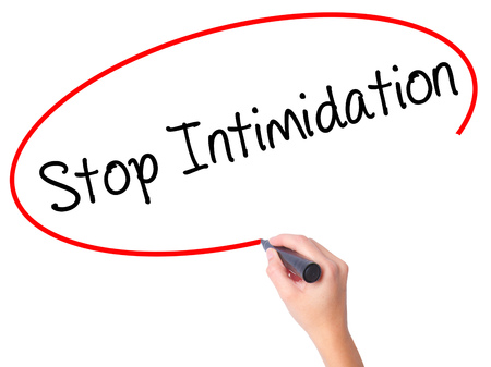 Women Hand writing Stop Intimidation with black marker on visual screen. Isolated on white. Business, technology, internet concept. Stock Photo Stock Photo