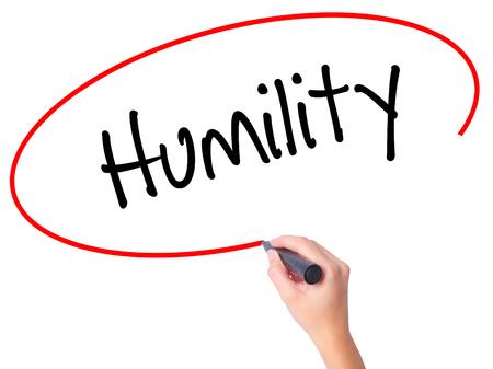 humildad: Mujeres mano escribiendo Humildad con marcador negro en la pantalla visual. Aislado en blanco. Negocios, la tecnolog�a, el concepto de internet. Foto de stock