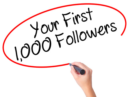 followers: Women Hand writing Your First 1,000 Followers  with black marker on visual screen. Isolated on white. Business, technology, internet concept. Stock Photo Stock Photo