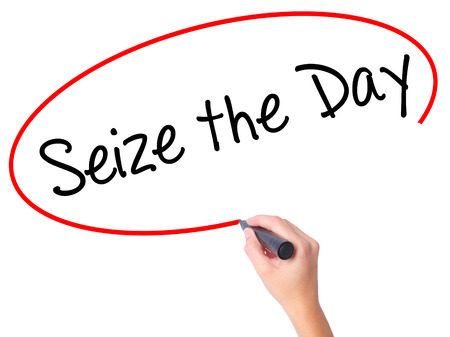 Women Hand writing Seize the Day with black marker on visual screen. Isolated on white. Business, technology, internet concept. Stock Photo Stock Photo