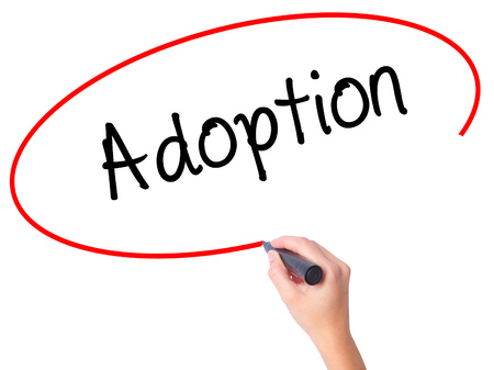 foster parenting: Women Hand writing Adoption with black marker on visual screen. Isolated on white. Business, technology, internet concept.