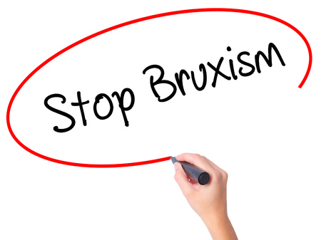 Women Hand writing Stop Bruxism with black marker on visual screen. Isolated on white. Business, technology, internet concept. Stock Photo Stock Photo