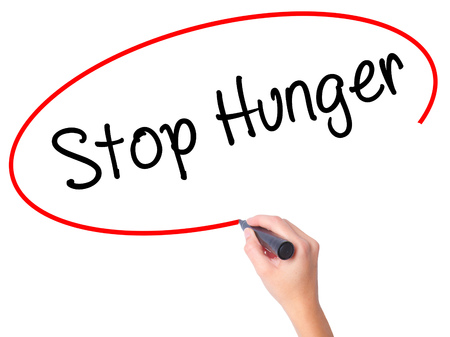 fight hunger: Women Hand writing  Stop Hunger with black marker on visual screen. Isolated on white. Business, technology, internet concept. Stock Photo Stock Photo