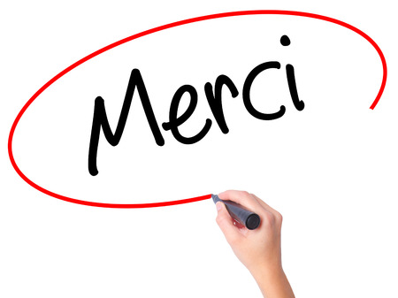 Women Hand writing Merci  (Thank You In French) with black marker on visual screen. Isolated on white. Business, technology, internet concept. Stock Photo