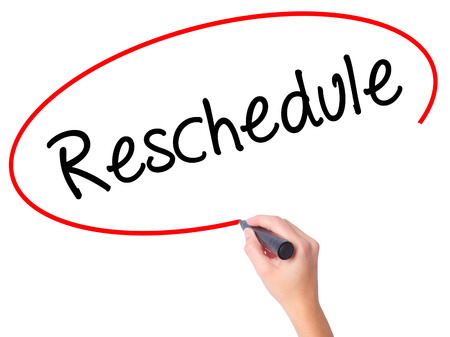 rescheduling: Women Hand writing Reschedule  with black marker on visual screen. Isolated on white. Business, technology, internet concept. Stock Photo