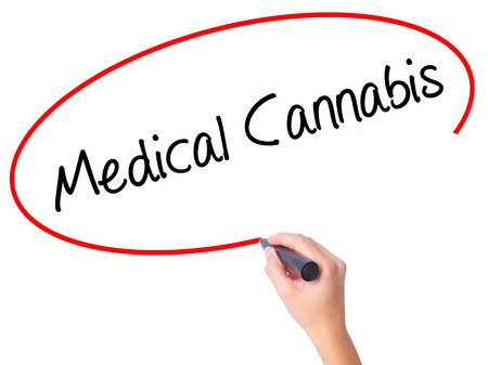 legislators: Women Hand writing Medical Cannabis with black marker on visual screen. Isolated on white. Business, technology, internet concept. Stock Photo