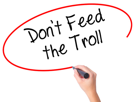ludicrous: Women Hand writing Dont Feed the Troll with black marker on visual screen. Isolated on white. Business, technology, internet concept. Stock Photo