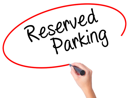 Women Hand writing Reserved Parking with black marker on visual screen. Isolated on white. Business, technology, internet concept. Stock Photo
