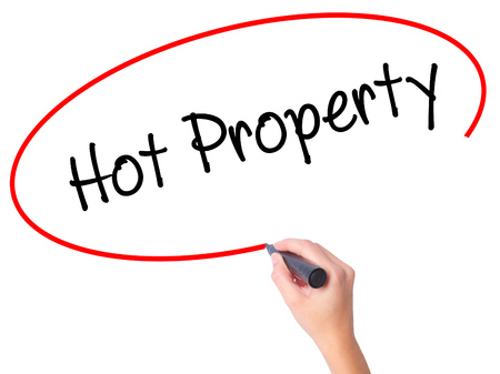 Women Hand writing Hot Property with black marker on visual screen. Isolated on white. Business, technology, internet concept. Stock Photo