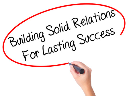 lasting: Women Hand writing Building Solid Relations For Lasting Success with black marker on visual screen. Isolated on white. Business, technology, internet concept. Stock Image