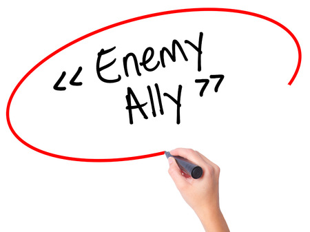 Women Hand writing Enemy - Ally with black marker on visual screen. Isolated on white. Business, technology, internet concept. Stock Photo Stock Photo