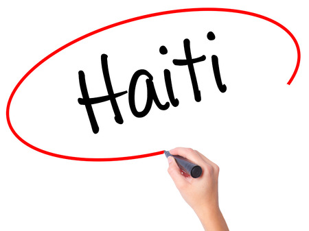 Women Hand writing Haiti with black marker on visual screen. Isolated on white. Business, technology, internet concept. Stock Photo