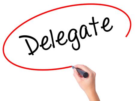 delegado: Mujeres mano escribiendo Delegado con marcador negro en la pantalla visual. Aislado en blanco. Negocios, la tecnología, el concepto de internet. Foto de stock