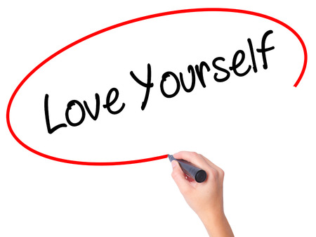 egoista: Women Hand writing Love Yourself with black marker on visual screen. Isolated on white. Business, technology, internet concept. Stock Photo Foto de archivo