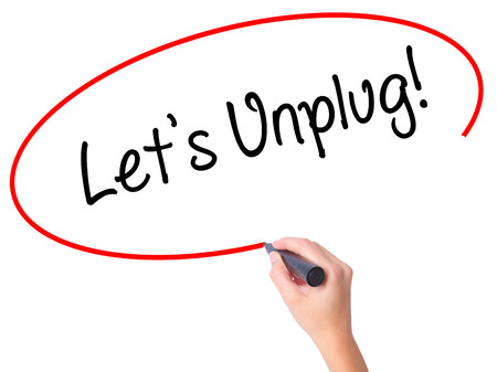 unplug: Women Hand writing Lets Unplug! with black marker on visual screen. Isolated on white. Business, technology, internet concept. Stock Photo