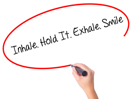 exhale: Women Hand writing Inhale Hold It Exhale Smile with black marker on visual screen. Isolated on white. Business, technology, internet concept. Stock Photo Stock Photo