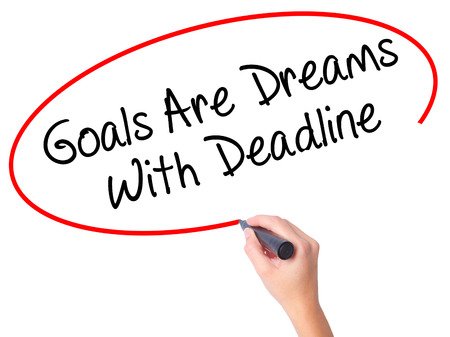 Women Hand writing Goals Are Dreams With Deadline with black marker on visual screen. Isolated on white. Business, technology, internet concept. Stock Photo