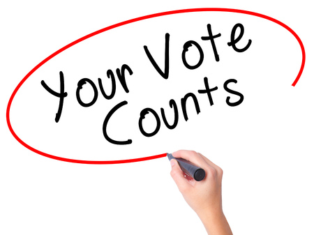 libertarian: Women Hand writing Your Vote Counts with black marker on visual screen. Isolated on white. Business, technology, internet concept. Stock Image