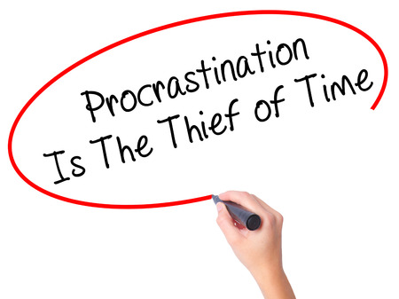 Women Hand writing  Procrastination Is The Thief of Time with black marker on visual screen. Isolated on white. Business, technology, internet concept. Stock Image Stock Photo