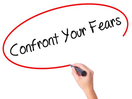 confront: Women Hand writing Confront Your Fears with black marker on visual screen. Isolated on white. Business, technology, internet concept. Stock Photo
