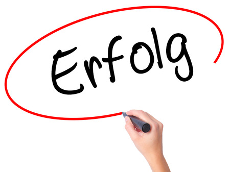 Women Hand writing Erfolg Success (in German) with black marker on visual screen. Isolated on white. Business, technology, internet concept. Stock Photo