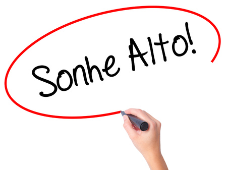 Women Hand writing Sonhe Alto! (Dream Big in Portuguese) with black marker on visual screen. Isolated on white. Business, technology, internet concept. Stock Photo