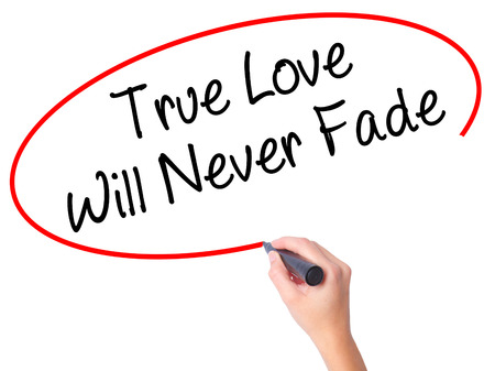 need direction: Women Hand writing True Love Will Never Fade with black marker on visual screen. Isolated on white. Business, technology, internet concept. Stock Photo