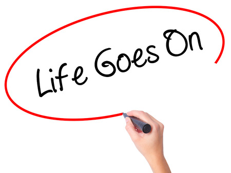 Women Hand writing Life Goes On with black marker on visual screen. Isolated on white. Business, technology, internet concept. Stock Photo Stock Photo