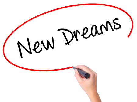 Women Hand writing New Dreams with black marker on visual screen. Isolated on white. Business, technology, internet concept. Stock Photo
