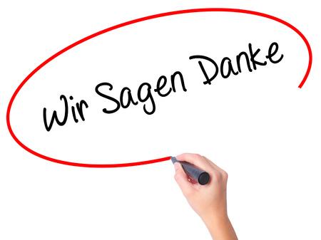 Vrouwen Hand schrijven Wir Sagen Danke (we zeggen bedankt in het Duits) met zwarte stift op visuele scherm. Geïsoleerd op wit. Business, technologie, internet concept. Stock foto