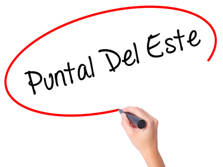 accommodating: Women Hand writing Puntal Del Este with black marker on visual screen. Isolated on white. Business, technology, internet concept.