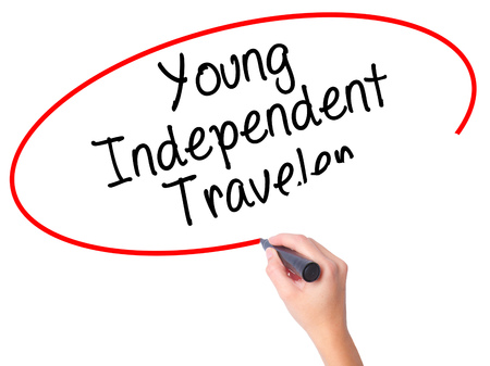 Women Hand writing Young Independent Traveler with black marker on visual screen. Isolated on white. Business, technology, internet concept. Stock Photo