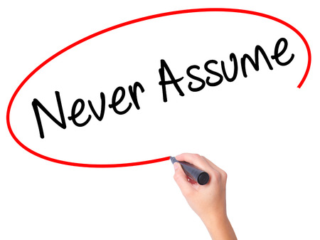assume: Women Hand writing Never Assume with black marker on visual screen. Isolated on white. Business, technology, internet concept. Stock Photo Stock Photo