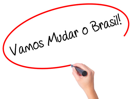 protestors: Women Hand writing Vamos Mudar o Brasil! (Lets Change Brazil in Portuguese)  with black marker on visual screen. Isolated on white. Business, technology, internet concept. Stock Photo