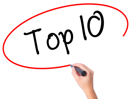 Women Hand writing Top 10 with black marker on visual screen. Isolated on white. Business, technology, internet concept. Stock Photo Standard-Bild