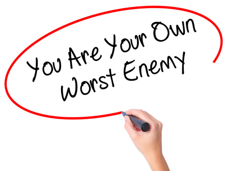 the worst: Women Hand writing You Are Your Own Worst Enemy with black marker on visual screen. Isolated on white. Business, technology, internet concept. Stock Photo