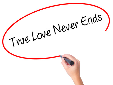Women Hand writing True Love Never Ends with black marker on visual screen. Isolated on white. Business, technology, internet concept. Stock Photo