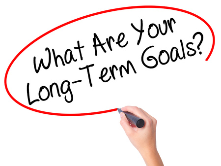 Women Hand writing What Are Your Long-Term Goals? with black marker on visual screen. Isolated on white. Business, technology, internet concept. Stock Photo